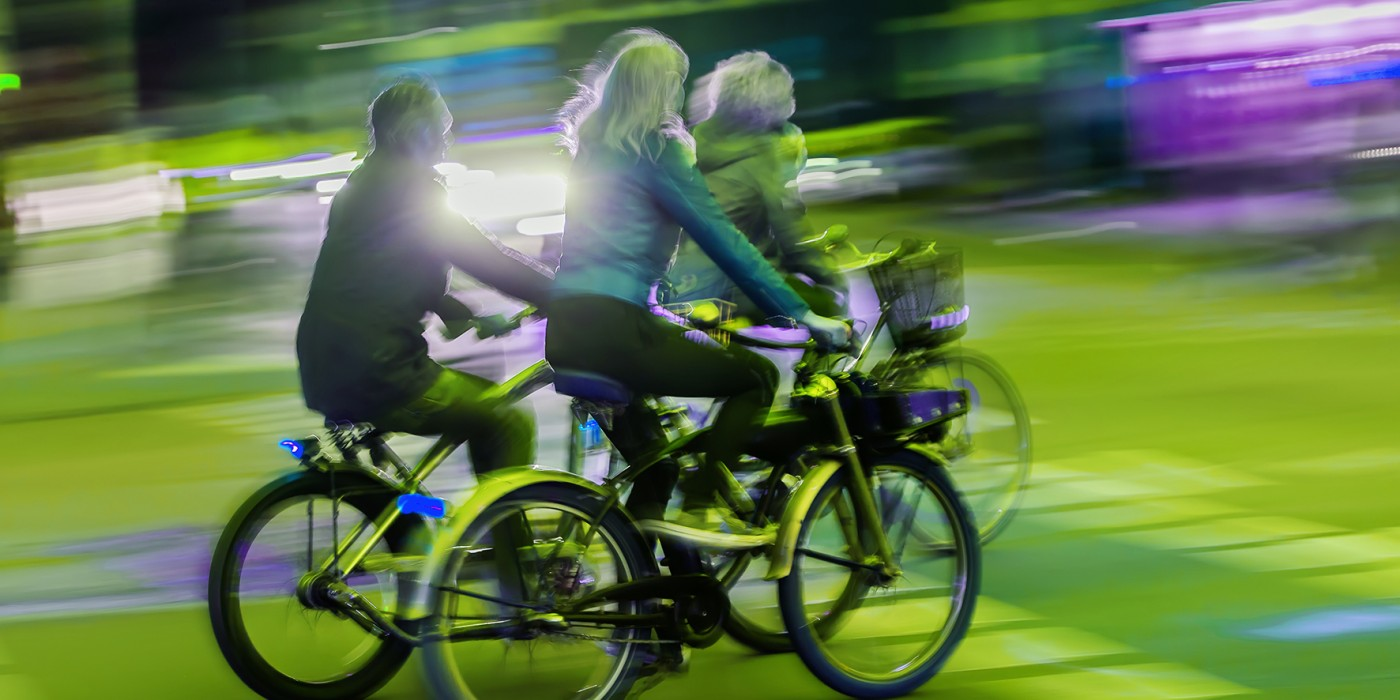 group of bicycle riders on a city street at night